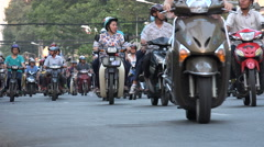 Motorbikes ride through the busy streets of Ho Chi Minh City in Vietnam Stock Footage