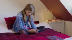 Young girl sitting cross legged on bed on smartphone. - stock footage