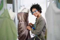Fashion designer working on a dress Stock Photos