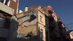 Worker on cherry picker knock down pieces from building wall, low angle shot Stock Footage