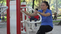 Senior Asian woman exercise on public fitness machine in Saigon park, Vietnam Stock Footage