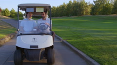Two men riding in a golf cart Stock Footage