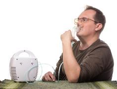 Adult man using inhalter Stock Photos