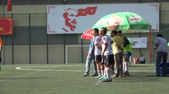 People play soccer (football) in front of Communist Party banner in Vietnam Stock Footage