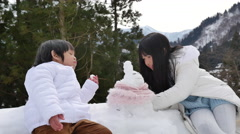 Cute asian sibling in winter clothes making a little snowman with old village Stock Footage