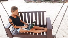 A young woman is sitting on a swing while working on a laptop.  She is raising a - stock footage