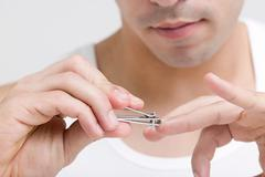 Man clipping his finger nails - stock photo