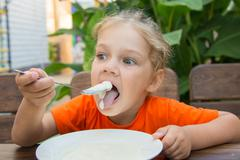 Five-year girl have fun and enjoy eating porridge for breakfast - stock photo