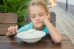 Upset six year old girl looking sadly at the semolina in a spoon at breakfast Stock Photos