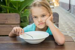 Six year old girl does not want to eat porridge for breakfast Stock Photos