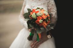 Pretty good wedding bouquet of various flowers in hand - stock photo