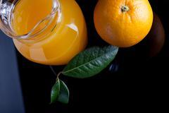Pitcher of fresh orange juice on black background top view Stock Photos