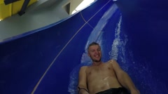 Happy Smiling Man Sliding in Water Attraction in Aqua Park. Slow Motion Stock Footage