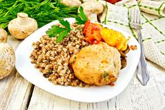 Cutlets of turkey with buckwheat in plate on board - stock photo