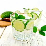 Lemonade with cucumber and mint in two glassful on board - stock photo