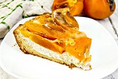Pie with curd and persimmons in plate on board - stock photo