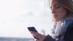 Young woman on her phone as a cable car passes in the background, in slow motion Stock Footage