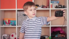 Little boy photographing himself makes selfie - stock footage