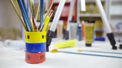 Table with paint brushes jar and color tubes 4K Stock Footage