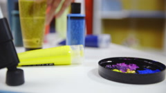 Hands squeeze color tube on plastic cap closeup 4K Stock Footage