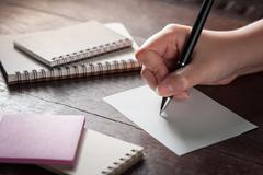 Female hand writing on paper - stock photo