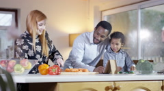 4K Happy mixed ethnicity family preparing a meal together in kitchen Stock Footage