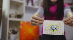 Female artist exhibiting painted picture card in hands 4K Stock Footage