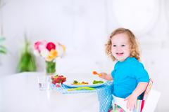 Little girl eating salad for lunch Stock Photos