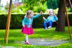 Kids on playground swing - stock photo