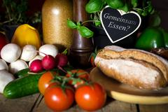 a lots of healthy and fresh vegetables and a rustic bread on a old wooden tab - stock photo