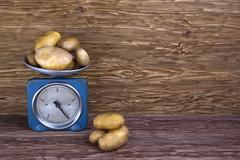 fresh potatoes on vintage scale and wood background - stock photo