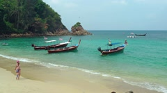 Tourists stroll along the sand of a rocky, tropical beach with longtail boats Stock Footage