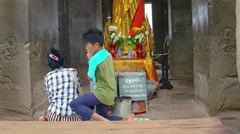 Pair of children praying before Buddhist altar inside Angkor Wat temple - stock footage