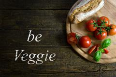 Tomatoes with bread on wooden table, Text be veggie Stock Photos
