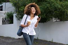 Cheerful young african woman listening music on city street Stock Photos