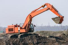 red excavator digs the ground - stock photo