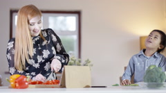4K Happy mixed ethnicity mother & son singing while preparing a meal in kitchen Stock Footage