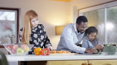 4K Happy mixed ethnicity family preparing a meal together in kitchen - stock footage