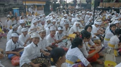 Many balinese children and adults sit on a floor in Pura Goa Lawah Stock Footage