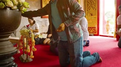 Buddhist worshippers kneel and give offerings before altar at Wat Chalong Stock Footage