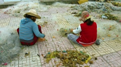 Local women clean debris from fishing nets at the end of a work day. - stock footage