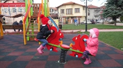 Children have fun playing swaying on a street park playground Stock Footage