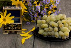 plate with grapes, a casket and a bouquet of flowers - stock photo