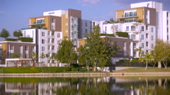 Static establishing shot of a luxury apartment complex reflecting in a lake Stock Footage