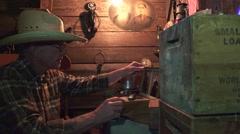 Cowboy in the bunkhouse , finds harmonica and plays Stock Footage