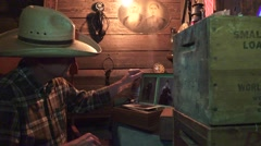 Cowboy in the bunkhouse , finds and plays harmonica Stock Footage