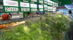 Fresh green vegetables sprayed with water in Vietnamese supermarket Stock Footage