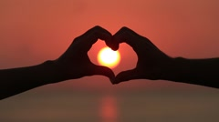 Making heart with hands over sun against beautiful sunset on horizon on the sea Stock Footage