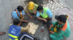 Vietnamese construction workers play traditional board game during lunch break Stock Footage