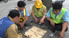 Lunch break, manual labor, construction workers, playing game, pavement, Vietnam - stock footage